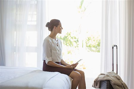 Businesswoman using digital tablet in hotel room Stock Photo - Premium Royalty-Free, Code: 6113-07731655