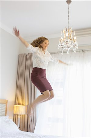 Businesswoman jumping on bed in hotel room Stock Photo - Premium Royalty-Free, Code: 6113-07731666