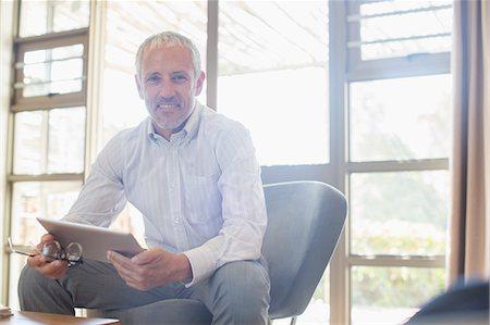 Businessman using digital tablet in living room Stock Photo - Premium Royalty-Free, Code: 6113-07731693