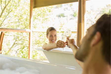 Couple toasting each other in bubble baths Stock Photo - Premium Royalty-Free, Code: 6113-07731602