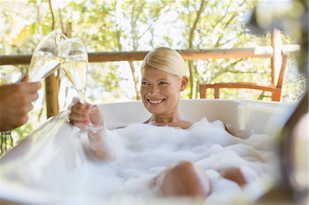 Couple toasting each other in bubble baths Stock Photo - Premium Royalty-Free, Code: 6113-07731615