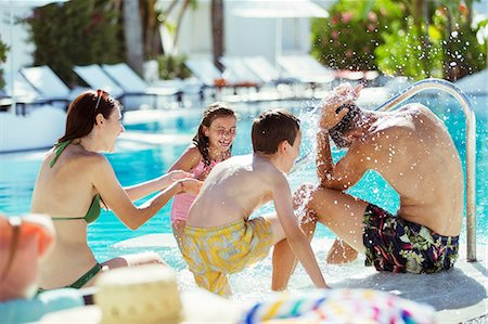 swimming pool water - Playful family with two children on poolside Stock Photo - Premium Royalty-Free, Code: 6113-07808097