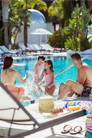 Family with two children splashing water in resort swimming pool Stock Photo - Premium Royalty-Free, Code: 6113-07808146
