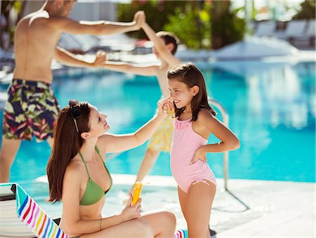 Mother applying suntan lotion on daughter's face by swimming pool Stock Photo - Premium Royalty-Free, Code: 6113-07808148