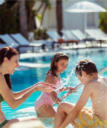 preteen girl topless - Family with two children splashing water in resort swimming pool Stock Photo - Premium Royalty-Free, Code: 6113-07808150