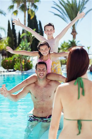 preteen family - Father giving piggyback ride to his two children in swimming pool Stock Photo - Premium Royalty-Free, Code: 6113-07808152