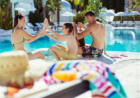 Family with two children enjoying themselves by swimming pool Stock Photo - Premium Royalty-Free, Code: 6113-07808157