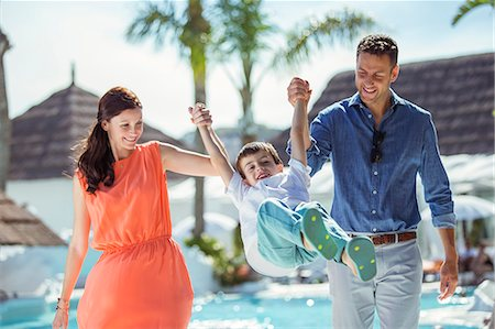 family  fun  outside - Boy holding hands with his parents by swimming pool Stock Photo - Premium Royalty-Free, Code: 6113-07808163