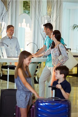 Family with suitcases talking with receptionist in hotel lobby Stock Photo - Premium Royalty-Free, Code: 6113-07808161