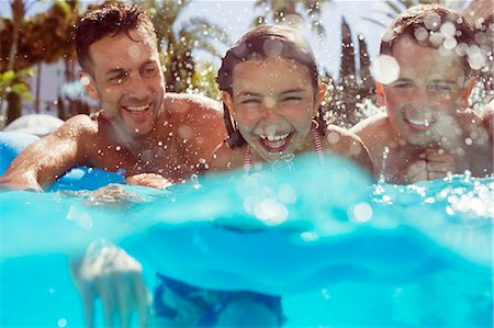 Father swimming with his two children in swimming pool Stock Photo - Premium Royalty-Free, Code: 6113-07808162