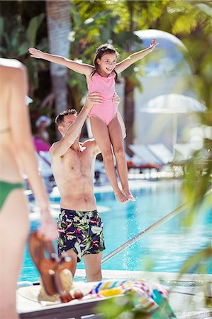 Father lifting smiling daughter by swimming pool Stock Photo - Premium Royalty-Free, Code: 6113-07808103