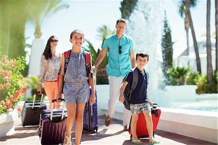 Family with suitcases passing by fountain in tourist resort Stock Photo - Premium Royalty-Free, Code: 6113-07808100
