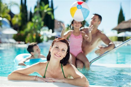 Portrait of smiling woman in swimming pool, family playing with beach ball in background Stock Photo - Premium Royalty-Free, Code: 6113-07808107