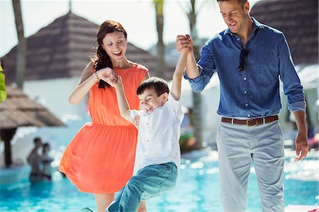 elementary age - Little boy having fun with his parents by swimming pool Stock Photo - Premium Royalty-Free, Code: 6113-07808106