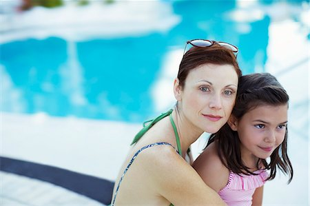 Portrait of mother and daughter sitting by swimming pool Stock Photo - Premium Royalty-Free, Code: 6113-07808113