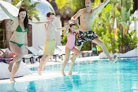 Parents with son and daughter holding hands, jumping into swimming pool Stock Photo - Premium Royalty-Free, Code: 6113-07808111