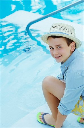 preteen thong - Portrait of smiling boy wearing straw hat crouching by swimming pool Stock Photo - Premium Royalty-Free, Code: 6113-07808120