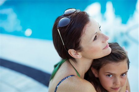 Pensive woman sitting by swimming pool with daughter Stock Photo - Premium Royalty-Free, Code: 6113-07808126
