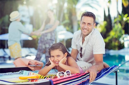 family  fun  outside - Portrait of smiling father and daughter relaxing by swimming pool, mother and daughter in background Stock Photo - Premium Royalty-Free, Code: 6113-07808130