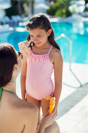 Mother applying suntan lotion on daughter's face by swimming pool Stock Photo - Premium Royalty-Free, Code: 6113-07808134