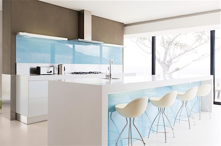 White and clean modern kitchen with stools at kitchen island Stock Photo - Premium Royalty-Free, Code: 6113-07808242