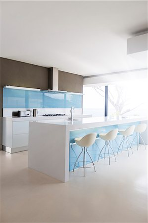 White and clean modern kitchen with stools at kitchen island Stock Photo - Premium Royalty-Free, Code: 6113-07808250