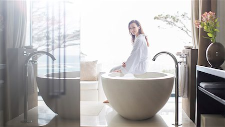 rich lifestyle - Portrait of smiling woman wearing white bathrobe, sitting on edge of bathtub in bathroom Stock Photo - Premium Royalty-Free, Code: 6113-07808266