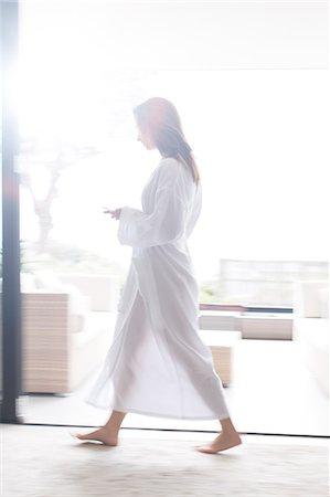 Woman wearing white bathrobe walking through modern corridor with mobile phone Stock Photo - Premium Royalty-Free, Code: 6113-07808207