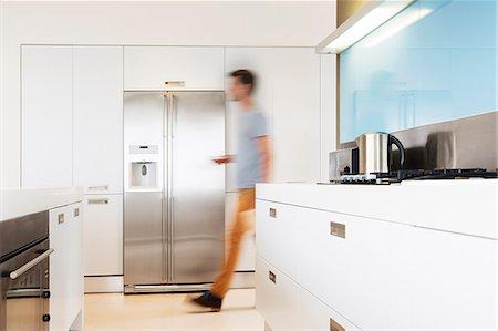 fridge - Man walking towards refrigerator in his modern kitchen Stock Photo - Premium Royalty-Free, Code: 6113-07808204
