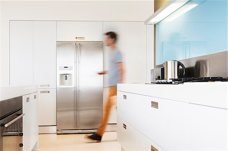 fridge - Man walking towards refrigerator in his modern kitchen Stock Photo - Premium Royalty-Free, Code: 6113-07808204
