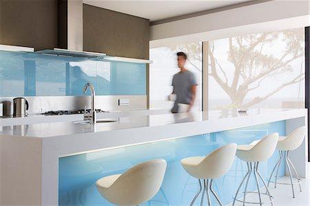 Blurred motion man walking through white and blue modern kitchen Stock Photo - Premium Royalty-Free, Code: 6113-07808225