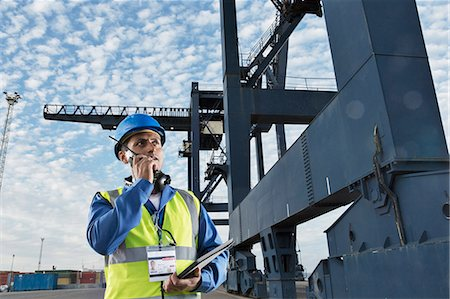 Worker using walkie-talkie under cargo crane Stock Photo - Premium Royalty-Free, Code: 6113-07808347