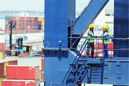 Worker and businessman shaking hands on cargo crane Stock Photo - Premium Royalty-Free, Code: 6113-07808371