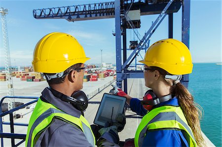 Workers using digital tablet on cargo crane Stock Photo - Premium Royalty-Free, Code: 6113-07808379