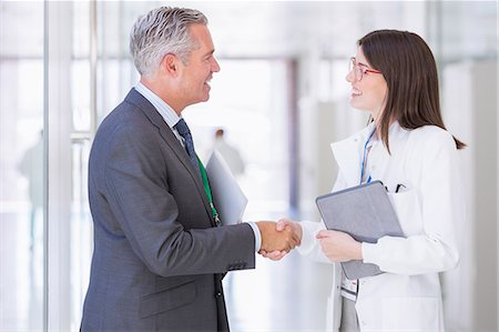 partnership - Scientist and businessman shaking hands in hallway Stock Photo - Premium Royalty-Free, Code: 6113-07808488