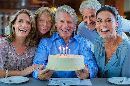 Portrait of smiling mature men and women with birthday cake Stock Photo - Premium Royalty-Free, Code: 6113-07808576