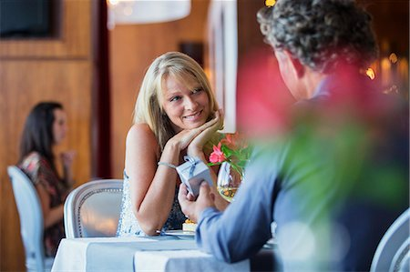Man giving gift to smiling woman at restaurant table Stock Photo - Premium Royalty-Free, Code: 6113-07808645