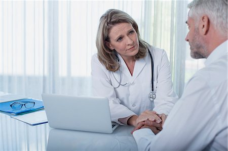 doctor and patient - Female doctor sitting at desk with laptop and consoling patient Stock Photo - Premium Royalty-Free, Code: 6113-07808653