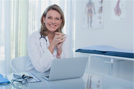 Portrait of smiling female doctor sitting at desk with laptop Stock Photo - Premium Royalty-Free, Code: 6113-07808659