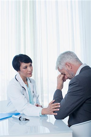 patient (medical) - Female doctor sitting at desk and consoling sad patient Stock Photo - Premium Royalty-Free, Code: 6113-07808664