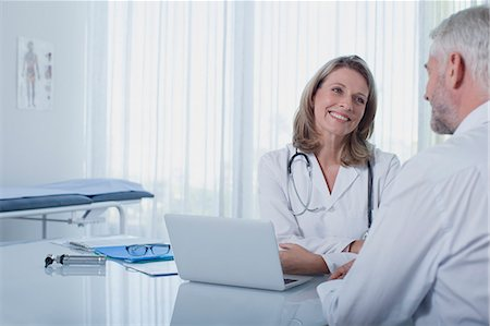 female doctor - Smiling female doctor talking to patient at desk in office Stock Photo - Premium Royalty-Free, Code: 6113-07808668