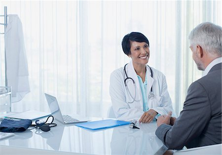 doctor and patients - Smiling female doctor talking to patient at desk in office Stock Photo - Premium Royalty-Free, Code: 6113-07808682