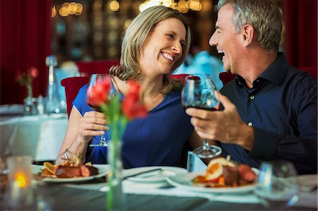 Smiling happy mature couple looking at each other and holding glasses with red wine in restaurant Stock Photo - Premium Royalty-Free, Code: 6113-07808608