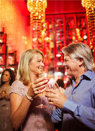 Mature couple standing face to face and holding drinks in nightclub Stock Photo - Premium Royalty-Free, Code: 6113-07808619