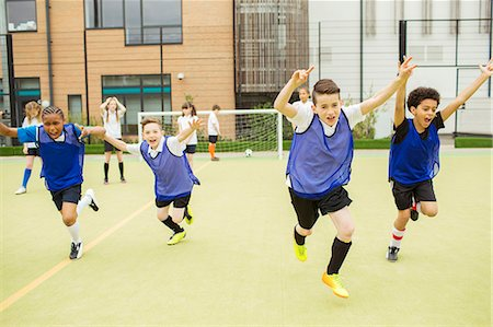Schoolboys wearing sport uniforms running with arms raised in soccer field in front of school Stock Photo - Premium Royalty-Free, Code: 6113-07808775