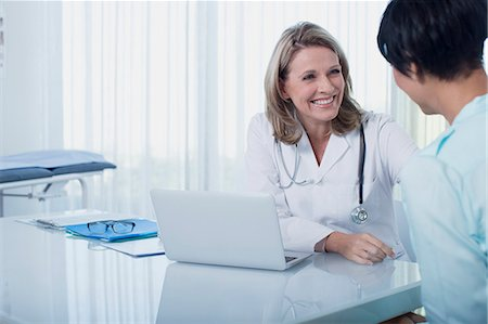 female doctor - Smiling female doctor and woman sitting at desk in office Stock Photo - Premium Royalty-Free, Code: 6113-07808703