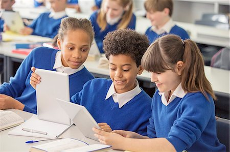 school girl uniforms - Elementary school children wearing blue school uniforms using digital tablets at desk in classroom Stock Photo - Premium Royalty-Free, Code: 6113-07961464
