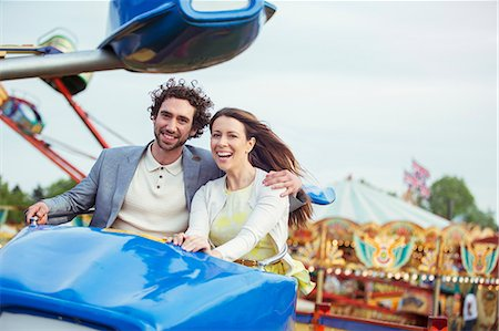 Couple enjoying ride on carousel in amusement park Stock Photo - Premium Royalty-Free, Code: 6113-07961560