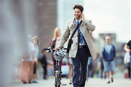 Businessman talking on cell phone pushing bicycle in city Stock Photo - Premium Royalty-Free, Code: 6113-07961595