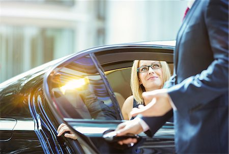 Chauffeur opening car door for businesswoman Stock Photo - Premium Royalty-Free, Code: 6113-07961659